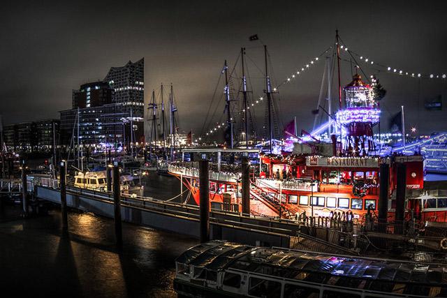 der-schiffsanleger-am-baumwall-eine-nachtaufnahme-viele-beleuchtete-schiffe-und-die-elbphilharmonie-im-hintergrund