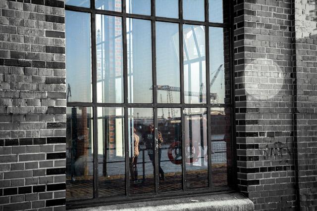 eine-mauer-und-ein-fabrikfenster-in-der-sich-zwei-menschen-spiegeln