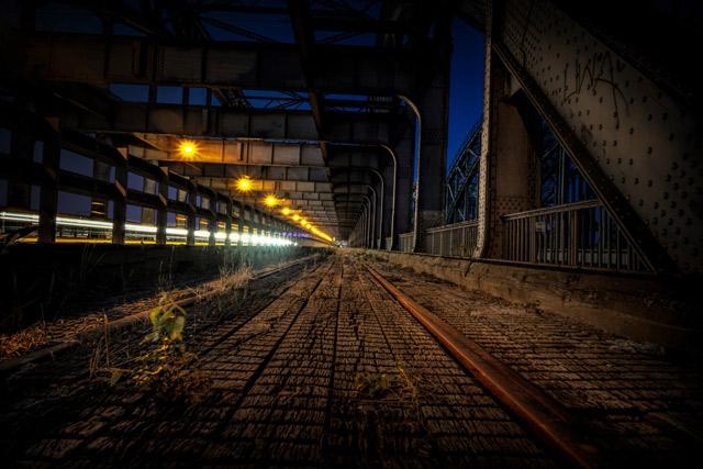 nachts-auf-einer-bruecke-auf-der-alte-gleise-fuehrt