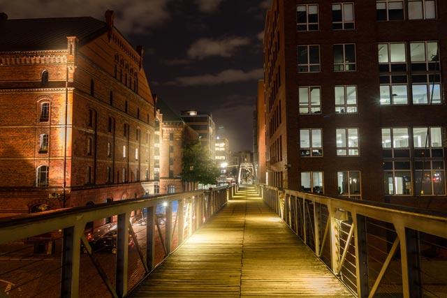 eine-lange-bruecke-durch-eine-haeuser-schlucht-nachts-in-der-speicherstadt