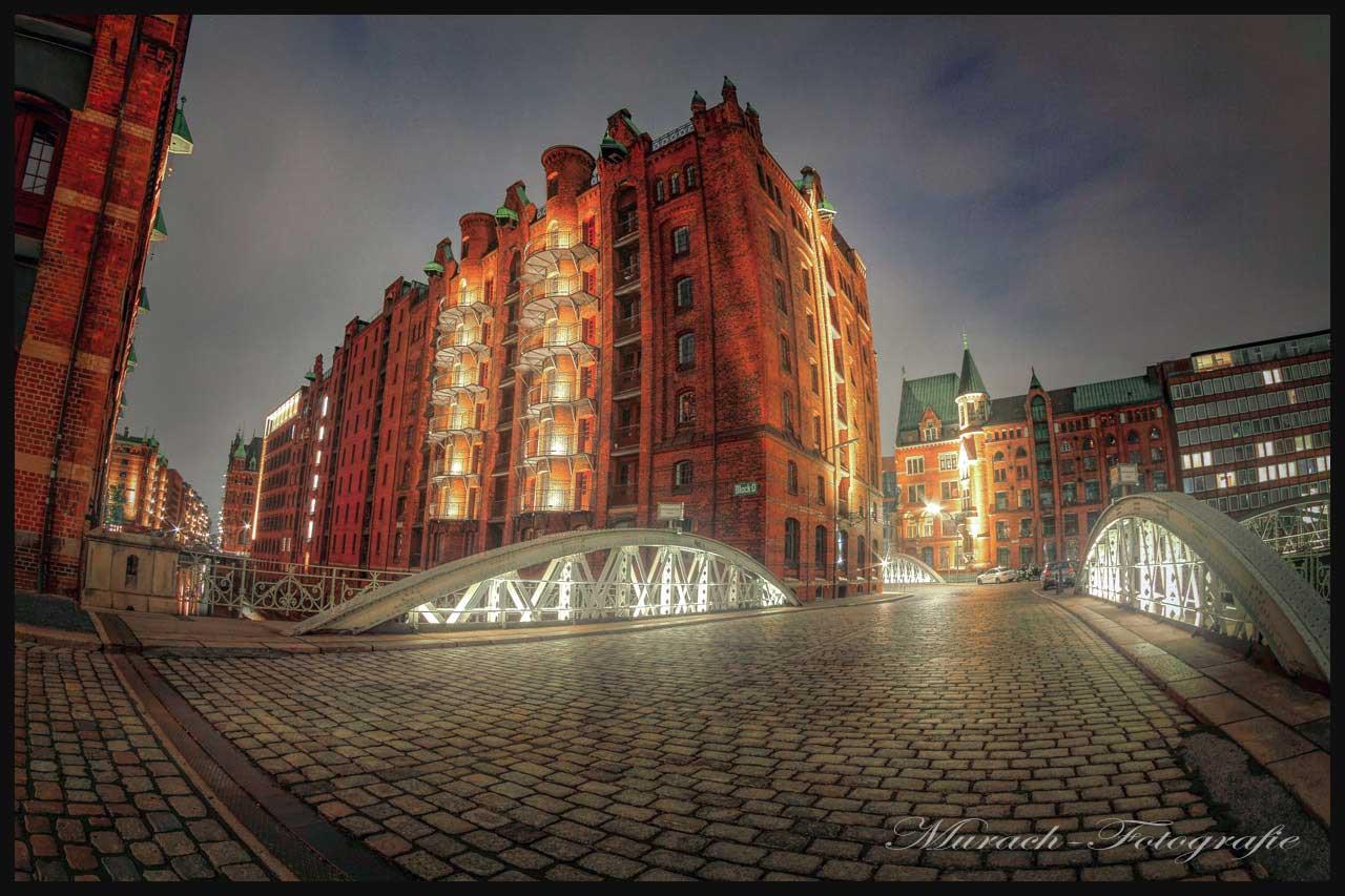 die-nachts-beleuchtete-speicherstadt-und-eine-kopfsteinpflasterstrasse-hamburg-wandbild-